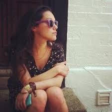 Kate Axelrod, the author, sits on a step wearing sunglasses