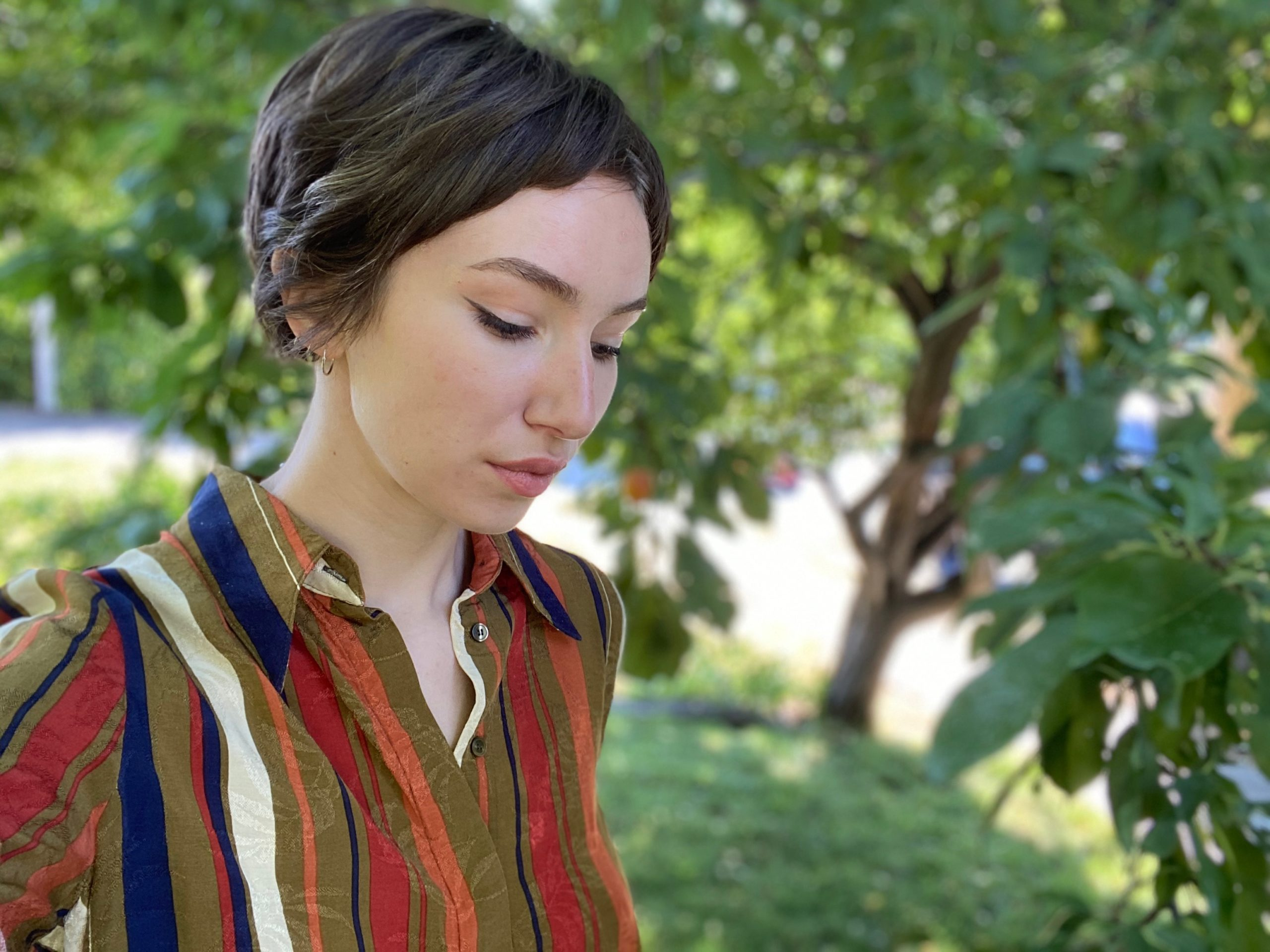 Effy is outside by trees in a striped brown, red, blue, and white shirt.