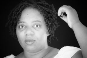 poet Vida Cross poses in a black and white photo playing with some of her curls