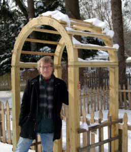 author Joseph Levens stands in front of a snowy arch