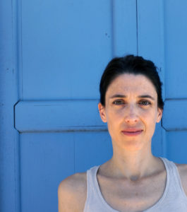 Photo of author Maria Ospina standing in front of a blue walll, taken by Simón Parra.