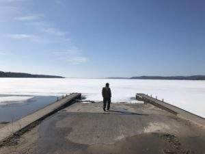 Daniel Wolff stands at the end of a pier by a frozen lake
