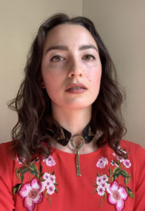 poet Gabrielle Bates looks into the camera wearing a red floral top