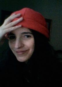 Poet Sara Kearns smiles at the camera in a red hat